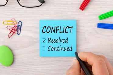 the word conflict on post-it note