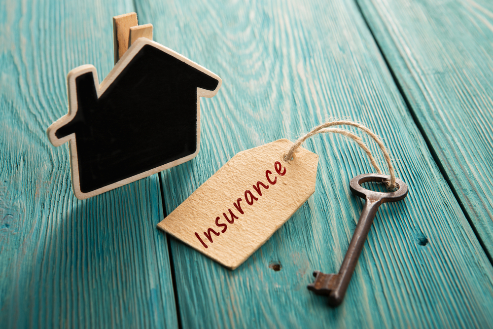 little house and old key - home insurance concept