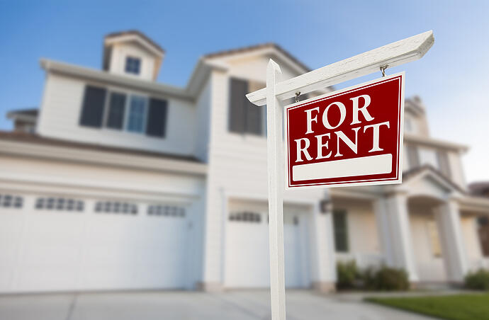red for rent sign in front of beautiful white single family home